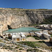 """Il-Qawra / Inland Sea - Das """"Inlandmeer"""" befindet sich nahe des Felsfensters Tieqa Żerqa / Azure Window. Durch einen Tunnel besteht Verbindung zum Meer. Um den kleinen See herum befinden sich zahlreiche Bootsschuppen und dergleichen."""