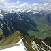 Im Südwesten - Westen: farbenfroher BREWald. Über dem frühlingsgrünen Talgrund von Schoppernau/Au noch schneegekrönte Gipfelkalotten.<br />Im Vordergrund stürzt der Westgrat in die Tiefe.