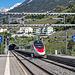 Warten auf den Bus am Bahnhof Leuk. Der Eurocity nach Venezia Santa Lucia saust vorbei.