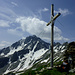Das schmucke Gipfelkreuz und ebensolcher Steinmann auf dem Piz Arlos. <br />Im Hintergrund die imposante Nordflanke des Piz Arblatsch