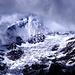 Die durch die Wolkendecke brechende Mittagssonne beleuchtet die Ostwand des Weisshorns (4505m), darunter der Bisgletscher.