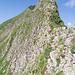 Dieses Bild zeigt den Aufstieg auf den schmalen Grat. Zuerst geht man leicht auf den Sattel vorn/oben im Bild. Ab dort hat es ein Stahlseil, welches links um den hohen Zacken fürht.