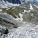 Das mühsame Geröllfeld zur Aufstiegsrinne von oben, das von der Alperschällilücke her kommend traversiert wird. Unten in der Mitte vom Schneefeld zwei Wanderer.