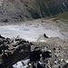 """Blick vom """"Vorgipfel"""" auf die schuttige Flanke. Der Weg verläuft eher links an der Abbruchkante zum Gletscher, der Übergang ins Eis erfolgt beim in der Bildmitte sichtbaren Schneefeld vor dem einzelnen Gratturm."""