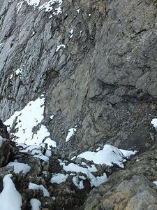 Bänderweg, zweiter Kessel, die Schlüsselstelle der ganzen Tour an diesem Tag. Der hier tiefer hinunter reichende braune Fels muss umgangen werden. Der Abstieg ist noch gut gestuft, der jenseitige Aufstieg ist heikel. Auf dem Hinweg sind wir auf dem grauen Fels mit abschüssigen, mit nur wenig Schutt beladenen Platten aufgestiegen. Im Rückweg sind wir der gesamten Grenzzone der Gesteine gefolgt, haben also oben bis in die Rinne in Bildmitte gequert und sind diese Abgestiegen; etwas, aber auch nicht viel besser (siehe auch übernächstes Bild und die Bilder des Abstiegs weiter unten).