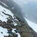 Bänderweg – Aufstieg zum Bifertenstock-Ostgrat. Der Bergsteiger (Rucksack) steht am Ende der Kette. Sicherungseisen führen um den Felsen davor herum, danach findet sich ein Schuttweglein.
