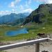 Ausblick von der Terrasse der Tilisuna Hütte. Im Vordergrund der vom Tilisuna Seehorn überragte Tilisuna See. Am Horizont die Berge rund um den Arlberg.