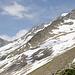 Hütte in Sicht, aber noch einiges an Weg vor uns. Der Weg verläuft zunächst Höhe haltend bis etwa Bildmitte, dann 50-80Hm nach unten einem Schneefeld folgend (wobei ein glatter Felsbereich umgangen wird), dann in einer Schuttrinne vor dem Felsgrat aufwärts, welcher sich von rechts oben bis in die Bildmitte schiebt (Südgrat Pointe Lanchettes). Auf Hüttenhöhe quert der Weg ein Felsband (mit Schild gekennzeichnet) und letztendlich über das Schneefeld zur Hütte.