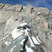 Zwischen den grauen Felsen im Vordergrund und der Gipfelwand  befindet sich eine hier nicht sichtbare kleine Felsscharte. Nun galt es, zunächst die heikel abschüssigen Felsen zu queren um dann über eine Felskante sehr unangenehm in die besagte Felsscharte abzusteigen. Die Felskante ist auf dem nächsten Bild zu sehen. Das schmale Felsband in der Gipfelwand zieht diagonal von der auffälligen waagerechten Felsplatte hinauf zum Gipfelkreuz.