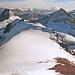 Wieder beim Abstieg geht der Blick über den breiten Bocktschingelgrat nach Süden bis zu den Gletschern um den Piz Medel.