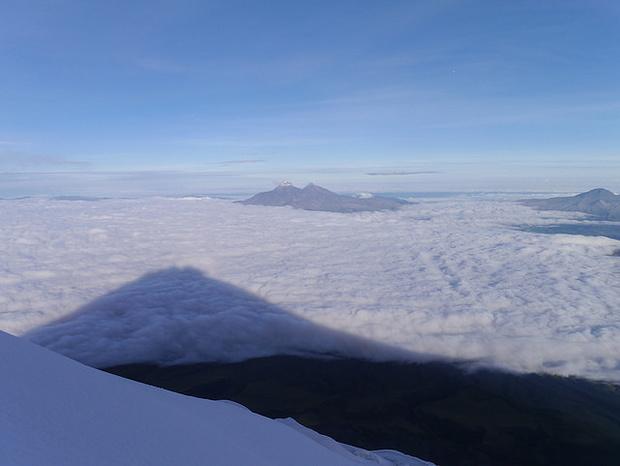 Auf den Wolken zeichnet sich der Schatten des Cotopaxi ab.
