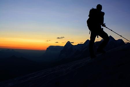 Ein Bergsteiger wartet auf den Sonnenaufgang.