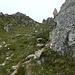 Eine erste Steilstufe führt zwischen den Felsen nach oben auf den Grat