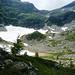 Bocchetta di Cattögn von der Alpe di Cansgai aus gesehen: Der Weg geht logisch durch den Graben links zum Altschnee und führt unterhalb der Felswand links aussen horizontal durch Geröll und Gras (jetzt behindert durch den Lawinenschnee)