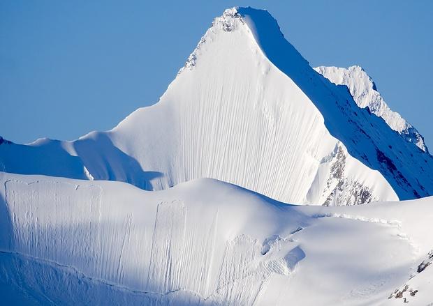 Das Matterhorn versteckt sich hinter dem Obergabelhorn, das seine steile Nordwand in ganzer Schönheit präsentiert. Im Vordergrund der Firngrat, der Blanc de Moming und L'Epaule du Zinalrothorn verbindet.