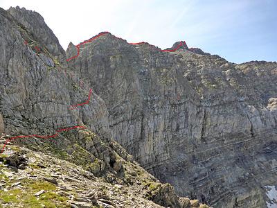 Luggen-Napoleon: Blick von der Schulter auf dem Nordwestgrat von P. 2702 auf den weiteren Routenverlauf bis zum Haldensteiner Calanda (Gipfelkreuz ist ganz rechts sichtbar). Zuerst geht es von der Schulter auf Rasenbänder in die Nordwestflanke. Dann feuchte Schroffencouloir aufwärts bis zu einem weiteren Grat. Dem sind wir nicht gefolgt, sondern in er Flanke aufwärts in den Sattel direkt südlich von P. 2702 hoch gestiegen (nicht im Bild). Napoleon ist nicht sichtbar, aber der Routenverlauf ab der tiefen Scharte P. 2706 direkt südlich vom Napoleon: über das exponierte Band und dann über Schutt hoch auf den Grat zum Haldensteiner Calanda. Unsere Route auf den (optionalen) Felsgrat zum Haldensteiner Calanda ist eingezeichnet, diesen könnte man auch über Schutt umgehen.