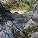 Sicht oberhalb der Felsbarriere auf 2000m hinunter auf den Geröllhang. Rechts erkennt man die Grasfläche über die wir aufgestiegen sind,