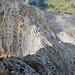 Blick hinunter auf das schmale Gratstück beim Abstieg. Zwei Wanderer üben sich gerade an diesem.