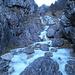 Ambiente alpino nelle Prealpi. Si passa sulle due pietre nel mezzo del fiume di ghiaccio.