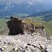 Im Abstieg durch den Steinhang auf die Leiter zu, danach führt der Weg über Wiesen abwärts.