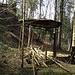 Im flachen Gelände unterhalb der Gratstrasse stösst man unvermittelt auf ein altes Eisengestell mit Dach: eine Art Gartenlaube mitten im Wald.