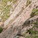 Mit rostigen Ketten gesicherte Querung über plattige Felsen.