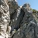Diese Wand zum Vorgipfel kann im Aufstieg in drei Varianten überwunden werden: Links durch das Felsenfenster (III), Gerade hoch den Bohrhaken nach (IV), oder rechts, am einfachsten aber luftig direkt über dem Abgrund (T6 II, oben ein BH). Im Abstieg...