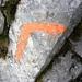 Blass-orange Zeichen und abgeschliffene Felsen zeigen den Weg