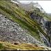 Der Weg führte im steten leichten Auf und Ab oberhalb der Felswände. Im Vordergrund eines der Blocksteinfelder mit den glitschigen Steinen.
