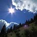 Die Sonne kommt hinter den Wolken hervor und auf dem steilen Anstieg wird es sofort sehr heiß. / Il sole spunta dietro le nuvole e sulla salita ripida subito si suda moltissimo.