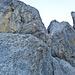 Solider Fels mit Fingerriss und Westrinne. Das beschriebene Fixseil baumelt über eine Steilstufe.