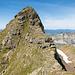 Rückblick zum ersten Steilstück im Abstieg vom Glogghüs. Abgestiegen wird im schrofigen Gelände ca. in der Mitte des Gipfelkopfs. Eine kurze Querung führt wieder zum Grat, der wenig unterhalb des Horizonts erreicht wird.