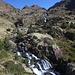 Im Aufstieg zwischen Refugi Vallferrera und Estany de Sotllo - Blick über den Bergbach am Plans de Sotllo. Im Hintergrund ist auch zu erkennen, dass dieser auf seinem Weg von den oberhalb gelegenen Seen einige Geländestufen mit kleinen Wasserfällen überwindet.