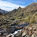 Am Estany d'Estats - Talblick am Abfluss des Sees. Hinten links dürfte der Monteixo (2.905 m) zu sehen sein, rechts der Pic de Pedres Blanques (2.755 m).