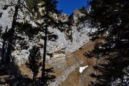 Man quert unter der Felswand und steigt in der Rinne etwas links oberhalb des Schneefelds hinauf.