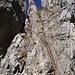 Il Caminetto Pagani, si deve passare per quella feritoia dove si vede una porzione di cielo azzurro. Due tronconi di scale separate fra loro permettono di arrivarci. Si noti come al fianco delle scale scorrino delle corde fisse che permettono di assicurarsi con eventuale set da ferrata.