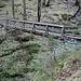 Brücke mit Aussicht aufwärts zu einem Wasserfall und einer Strassenbrücke