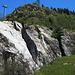 beim Start in Mörel, strahlend blwuer Himmel, warme Temperaturen und aus dem Fels fließt ein kleiner Wasserfall