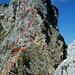 Der Verlauf des Klettersteigs. (unten) Ein Klettersteiggeher an der 1. Schlüsselstelle im Einstieg. Die 2. sehr luftige Schlüsselstelle eine Fingerbreite unter dem Gipfel (Route weicht über den SO-Grat kurz in die senkrechte Ostflanke aus).