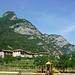 Ausblick vom Parkplatz in Biacesa di Ledro - im Hintergrund die Cima Capi. Der Klettersteig Sentiero Susatti beginnt im grünen Sattel (unteres Drittel) und folgt der Gratkante nach oben. Der Abstieg über die Sentiero delle Laste beginnt im Sattel unterhalb der Rocca verläuft irgendwo durch die gründurchsetzte Felsflanke. Die Lage Sentiero Foletti kann man nicht einsehen - liegt hinter der Rocca.