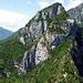 Der Weiterweg verläuft entlang der Gratkante -die nach Norden hin hunderte Meter senkrecht abfällt - immer in Schützengräben bzw. Befestigungsanlagen...stolpern verboten. An der Felswand links hinunter. Hier beginnt der Sentiero Foletti mit der Schlüsselstelle (Licht-Schattengrenze). An der Kante schräg nach oben - den Büschen folgend bis in die hintere Verschneidung, dort wieder abwärts. Links im Wald das Bivacco Arcione.