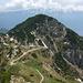 Im Osten der Corno della Marogna (1953m) mit der Tremalzopass-Strasse. Dahinter die schneebedeckte Gipfelkette des Monte Baldo über dem Gardasee.