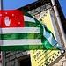 Die Flagge der Republik Abchasien. Die Hand steht für die abchasische Nation, die sieben Sterne stehen für die sieben Regionen des Landes und die Grünweissen Streifen für die Religionen Christentum und Islam. Heute sind nur noch 16% der Abchasen Moslems, da im die meisten muslimischen Abchasen schon im 19. Jahrhundert ausgewandert waren. 60% der Bevölkerung Abchasiens bezeichnet sich als Christen.