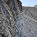 Der Weg führt knapp unter den schwarzen Felsen hindurch.