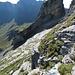 Blick auf die südöstliche Umgehung des Murmelchopfs. Man klettert die kleine Felsstufe unmittelbar im Vordergrund hinab, quert zu den Felsplatten in Bildmitte hinüber und folgt absteigend einer Rinne. Anschliessend klettert man auf der anderen Seite durch einen Riss wieder hinauf.