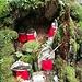 Impression aus dem Okuno-in (IX). Jizo-Figuren. Jizo kommt als Schutzgott im Buddhismus eine zentrale Funktion zu. Die roten Lätzchen sollen verstorbenen Kindern helfen, die den Fluss Sai no Kawara ins Paradies überqueren müssen.