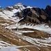 """Nachdem ich einige Höhenmeter auf dem Fahrsträsschen von der Bergstation First abgestiegen war, zeigte sich mir beim Distelboden der nächste Steckenabschnitt. Links von wenig kontrastreichen Grasgipfel des Schilts (2318m) in der Bildmitte galt es zunächst den Sattel zu erreichen. Genau über dem 2241m hohen Übergang steht der Gipfel des Schwarzhorens (2927,7m). Rechts im Bild steht der düstere Gemschberg (2658,7m) der viel """"schwärzer"""" als das Schwarzhoren in Erscheinung tritt."""