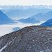 Ein Wanderer schiesst gerade ein Foto vom Mutschen aus. Im Hintergrund das Bernina Massiv.
