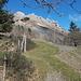 Etwas oberhalb des Parkplatzes führt ein Pfad an einem Zaun entlang zu einem Bergsturzgebiet, das überquert werden muss, damit man die im Bild sichtbare Felsbarriere rechts umgehen kann.