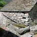 Lo vedremo più volte: un tetto a falda, una gronda di legno e una vasca monolitica....